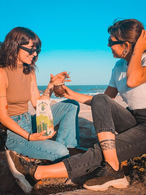 two friends with a mate gourd and a package of milonga yerba mate