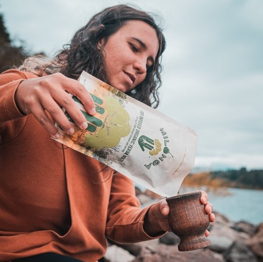 A girl putting yerba mate into a mate gourd of wood