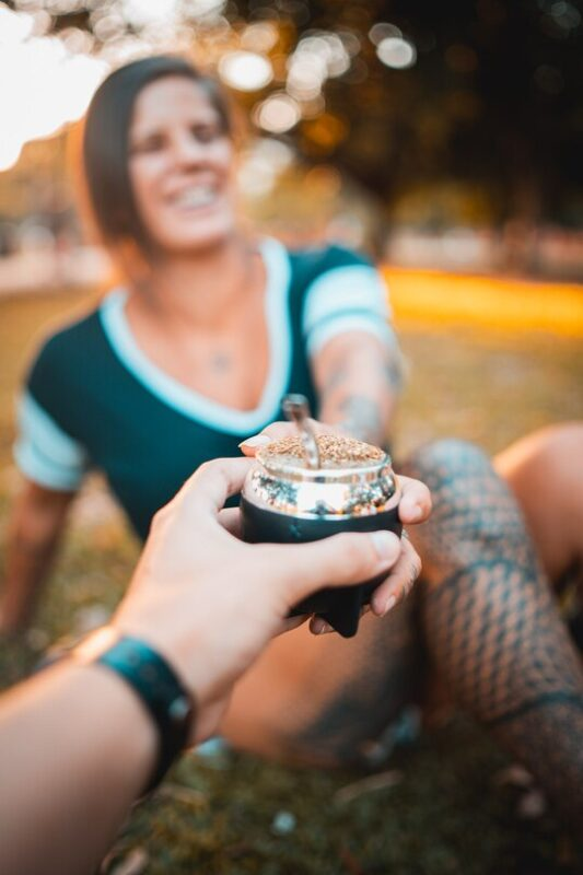 woman smiling and taking a mate gourd with yerba mate